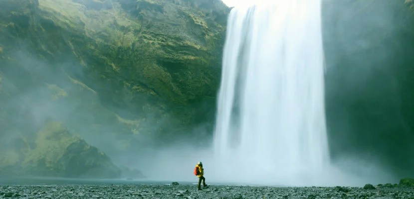 A female hiker is standing at a foot of a Skogafoss waterfall in Southern Iceland. Traveller looks very small in perspective with this majestic waterfall. Skogafoss is one of the best known and most popular waterfalls in Iceland and is here photographed on a cold windy day in winter of 2015. Longer exposure for the silky running water effect.