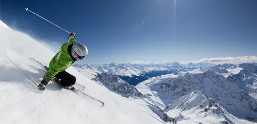Female skier on downhill race with sun and mountain view. New high resolution ski pictures: