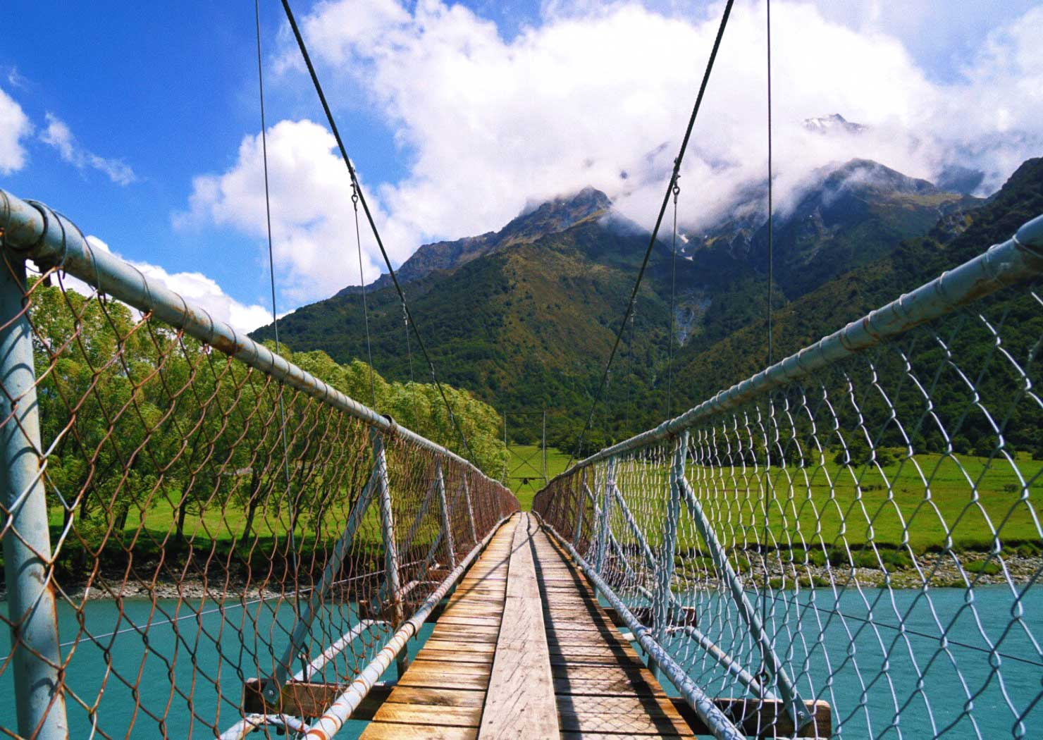 thereafterish, new zealand matukituki river running through matukituki valley and suspension bridge over river