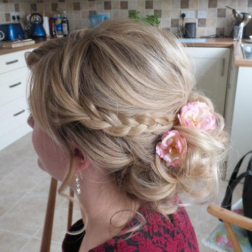 low curly updo with braid and flowers