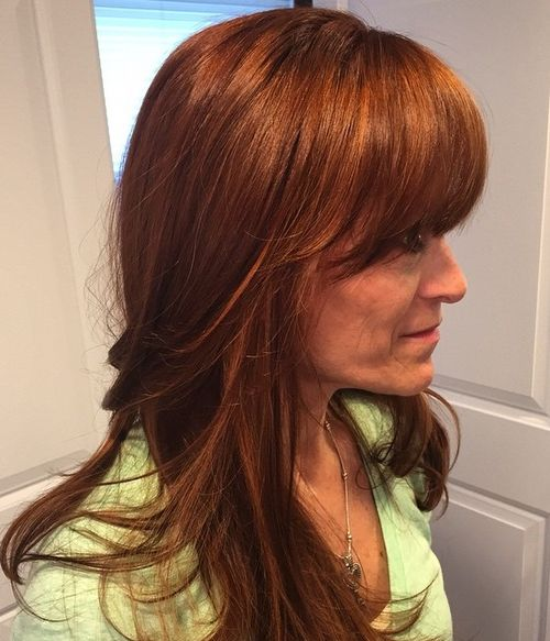 auburn layered hairstyle with full bangs