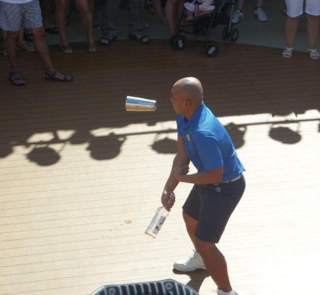 Norwegian Cruise ship staff member juggling on the pool deck