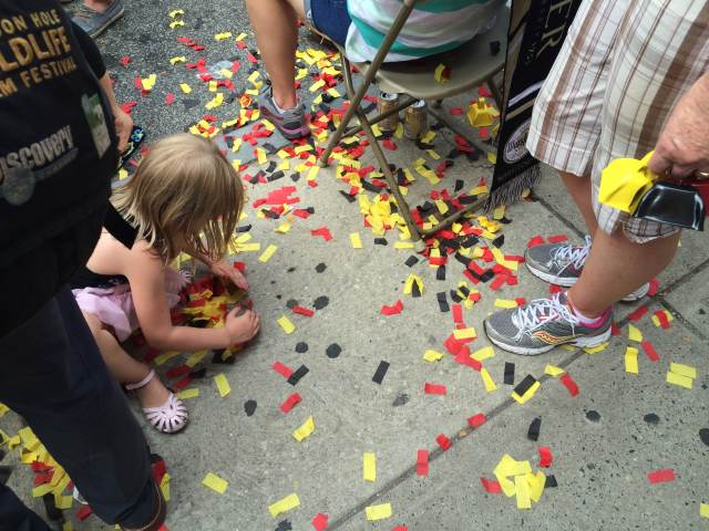 A girl picks up German-colored confetti from the ground prior to Sunday's game. (Adam Hermann - The Triangle)