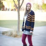 Looking cheerfully casual, Brynn is in a triple knit outfit. A cream knit sweater is juxtaposed over a grey knit dress while being wrapped in a navy and mustard horizontally-striped knit sweater. Coloured pants (in this case fuchsia) are a must-have to brighten any outfit during the drab winter months.