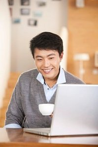 Man seated in front of a lap top with a cup of coffee and smiling.