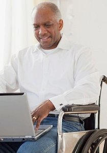 Man seated in a wheel chair, using a lap top computer.