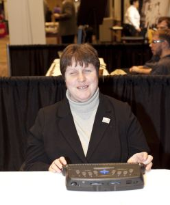 WeCo Lead Certified Test Consultant, using a Braille Display while testing for digital accessibility, and smiling.