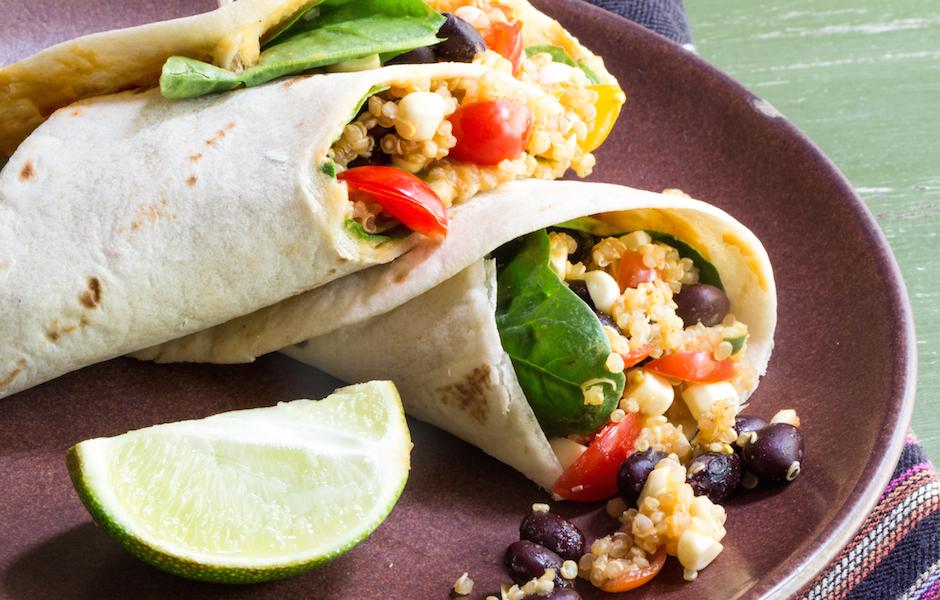 Vegan wrap with quinoa, black beans, hummus, corn, and tomatoes.