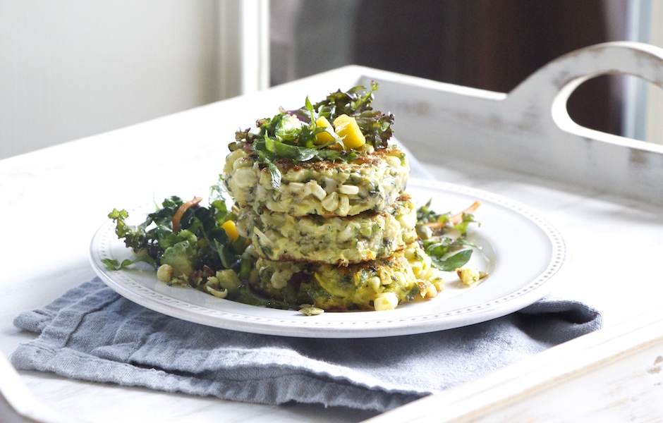 Corn and zucchini fritters topped with kale-avocado-mango salad.