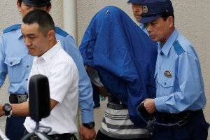 Satoshi Uematsu (C, with a jacket over his head), suspected of a deadly attack at a facility for the disabled, is escorted by police officers as he is taken from local jail to prosecutors, at Tsukui police station in Sagamihara, Kanagawa prefecture, Japan, July 27, 2016. Credits: REUTERS/Issei Kato