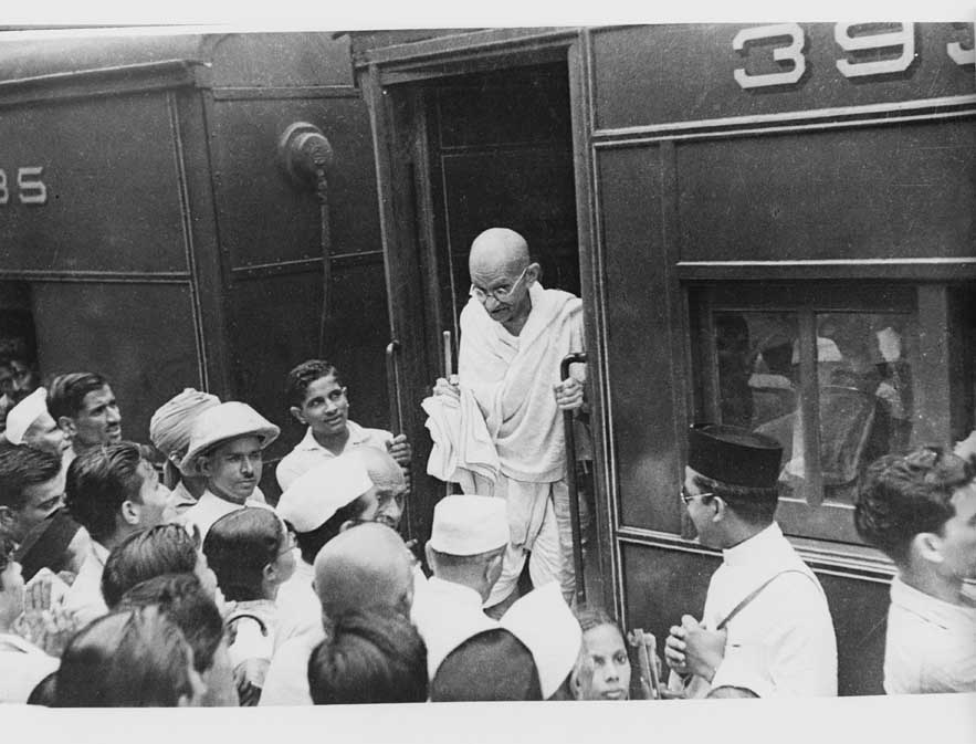 A crowd greets Gandhi as he alights at a station. Credit: Wikimedia Commons