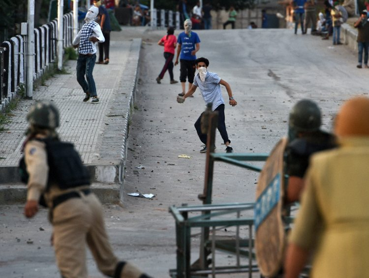 Youths throwing stones at security forces during a clash in Srinagar on Thursday. Credit: PTI/S. Irfan