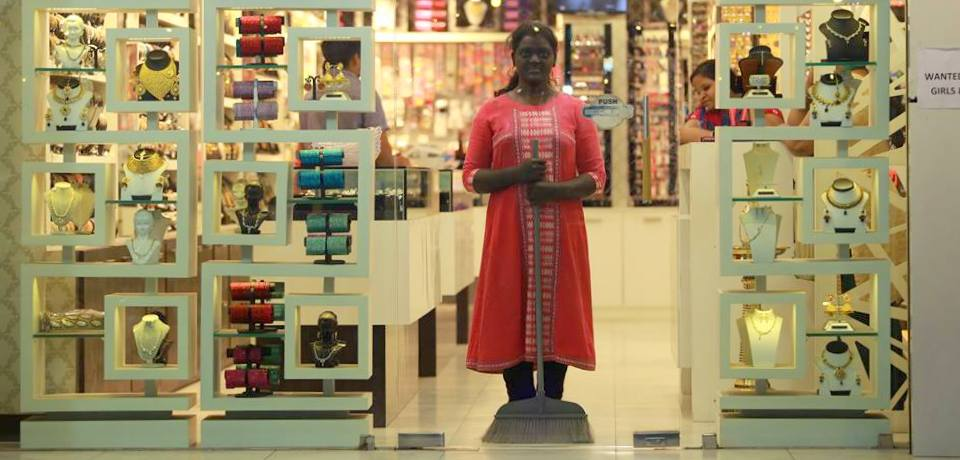 P.S. Jaya posing in a jewellery and cosmetics shop window with a painted face and body. Credit: Facebook