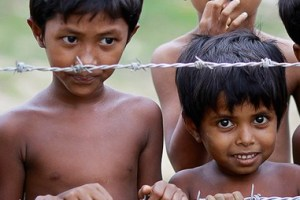 Children stand behind barbed wire outside a hospital in a camp for Muslims, outside Sittwe in May 2013. Credit: Reuters