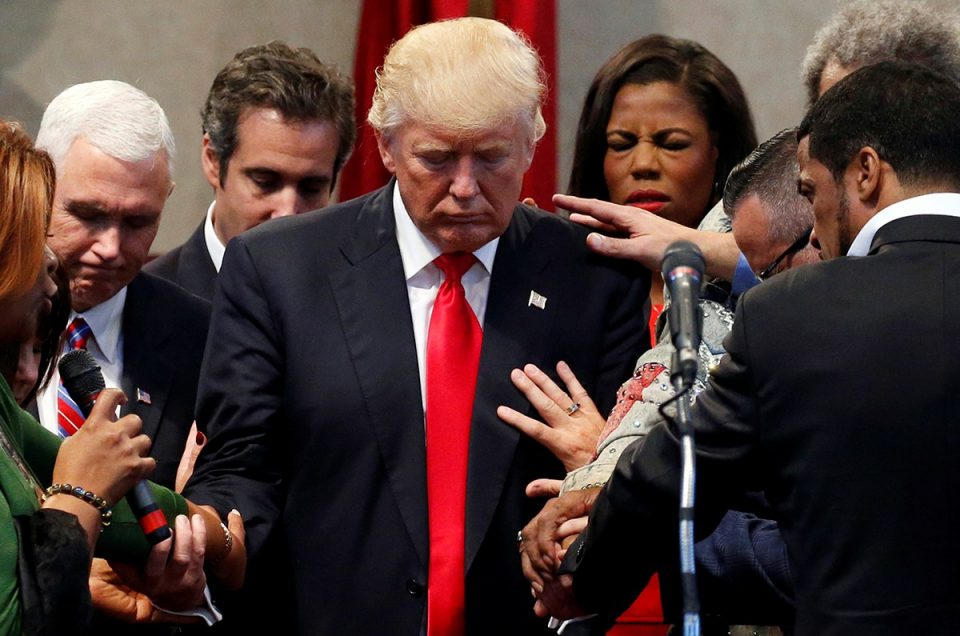 Members of the clergy lay hands and pray over Republican presidential nominee Donald Trump at the New Spirit Revival Center in Cleveland Heights, Ohio, U.S., September 21, 2016. REUTERS/Jonathan Ernst - RTSOT3J