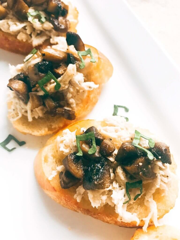 Ready in 20 minutes, this fast and easy appetizer is perfect for social gatherings like wine tastings! A great finger food that is simple to make, the baguette slices are toasted and topped with shredded chicken, mushrooms, butter, and sage. A great party appetizer and perfect to pair with wine. Buttered Chicken and Mushroom Crostini   Three Olives Branch   www.threeolivesbranch.com