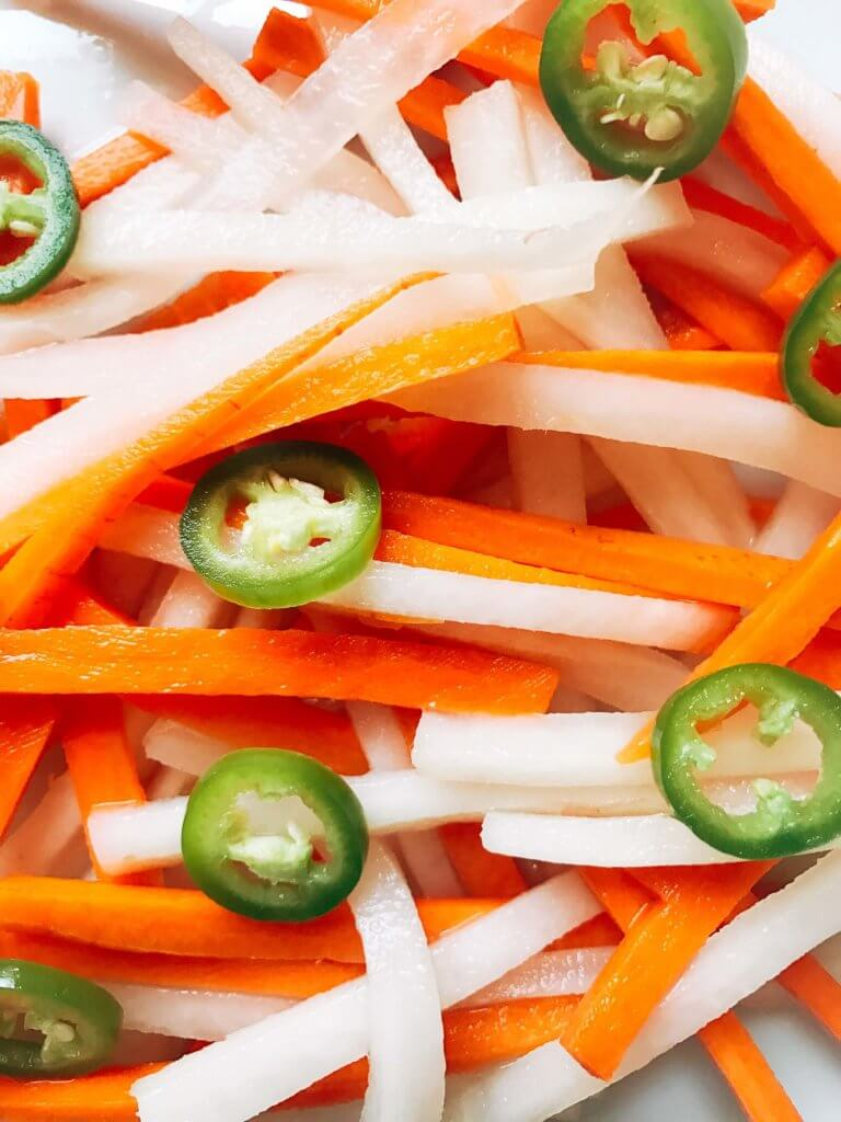 Simple and easy Spicy Vietnamese Pickled Vegetables perfect for your banh mi! Use as a quick condiment on your favorite foods. Quick refrigerator pickle of daikon radish and carrots are made spicy with serrano. A rice vinegar base is ready in just minutes for this classic Vietnamese slaw. Use cucumber or your favorite vegetables. Vegan, gluten free, and vegetarian. #pickled #banhmi #vietnamese
