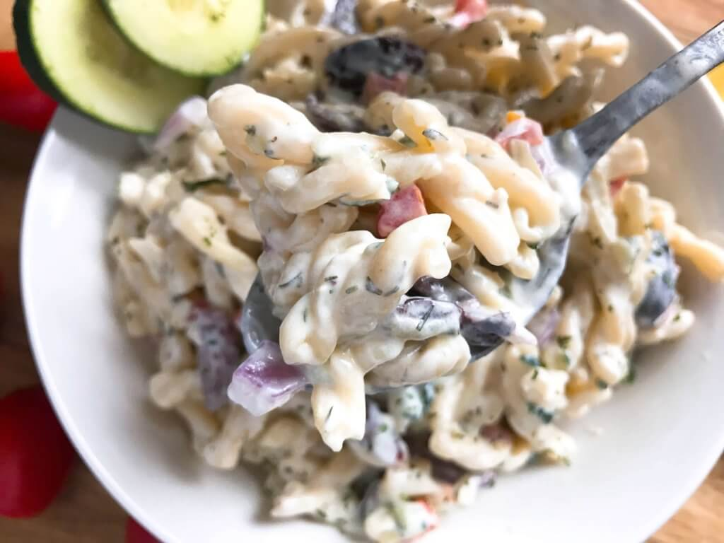 A simple side dish recipe for a BBQ or grilling party. Creamy Greek Tzatziki Pasta Salad is made with plain Greek yogurt tzatziki sauce, tomatoes, onion, cucumber, olives, and feta cheese. Make in advance for a healthier side. #bbqsides #grillingsides #pastasalad