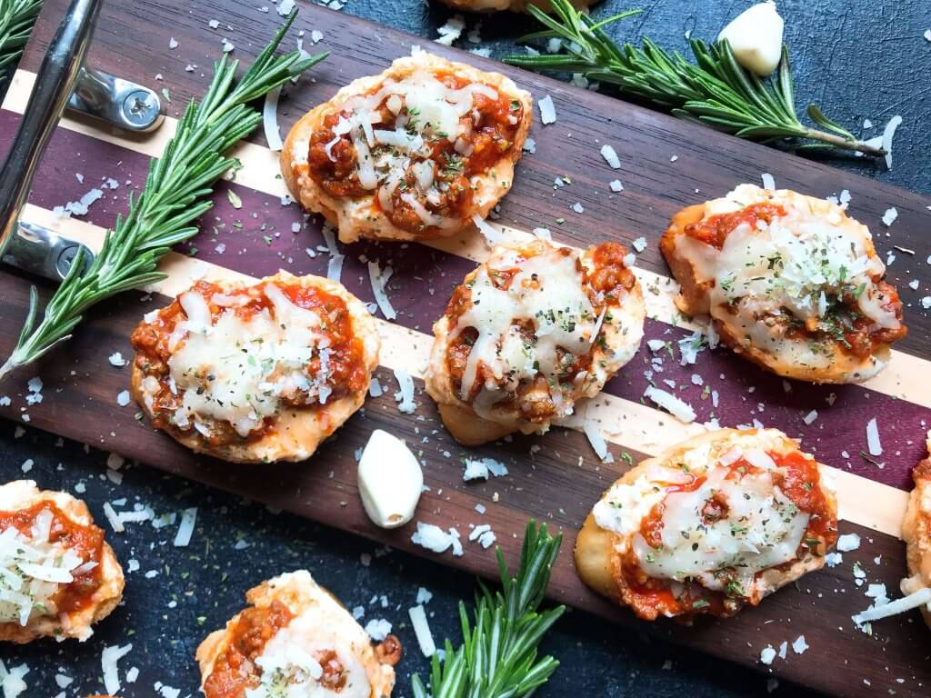 Quick and simple Simple Beef Lasagna Crostini are ready in less than 30 minutes. Ground beef is mixed in marinara and layered with three cheeses on bite sized appetizer toasts. Ricotta, mozzarella, and Parmesan cheeses make this a great entertaining or party food for game day and holidays. #lasagna #beefappetizer #partyfood