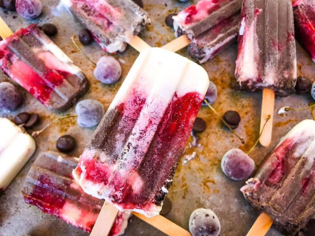 Black Forest Yogurt Popsicles are a simple and quick frozen dessert treat perfect for summer. Greek yogurt, cocoa chocolate yogurt, and cherry pie filling are layered for a healthy dessert. Vegetarian. #blackforest #cherrychocolate #popsicles