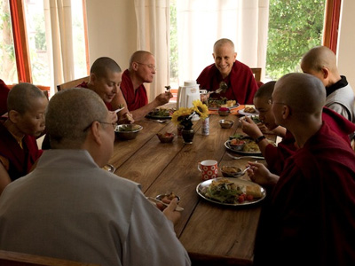 Venerable smiling while eating a meal with other monastics.