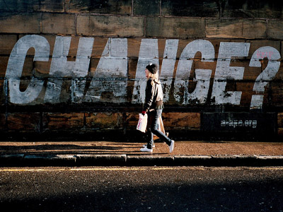 A woman walking on the road, there's a big white color word:CHANGE? on the side of the wall.