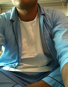 Young man sitting, wearing a blue hospital pajama.