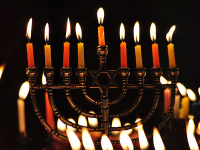A menorah with lit candles against a dark background.