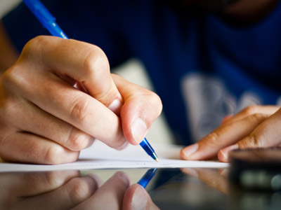 A hand holding a pen, writing on a piece of paper.