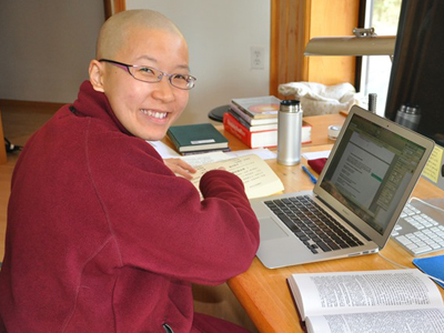 Venerable Damcho smiling, with a book and laptop.