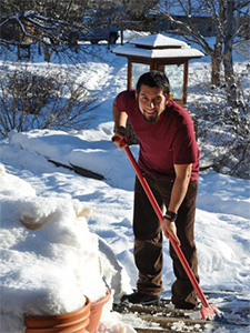 Winter retreatant, Isaac, cleaning snow from a walkway.