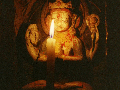 Candle offering to small statue of Chenrezig.