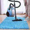 Man vacuuming a blue rug.