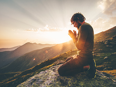 Man on a mountain at sunset, kneeling with palms together.