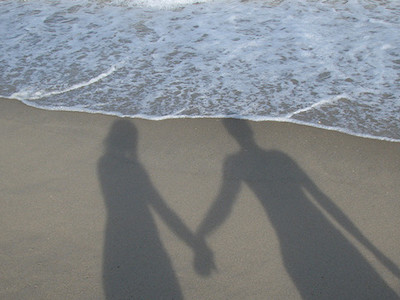 Silhouette of couple holding hands on the beach.