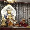 Venerable teaching in front of a large Buddha statue.