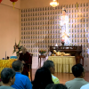 Venerable teaching in front of large Buddha statue.
