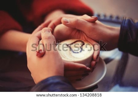 Four hands wrapped around a cup of coffee with heart drawing - stock photo