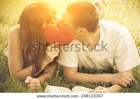Young couple in love kissing each other , hided behind heart toy pillow  - stock photo