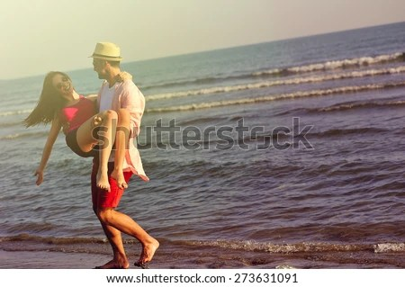 Beautiful young couple in love enjoying and having fun at the beach - stock photo