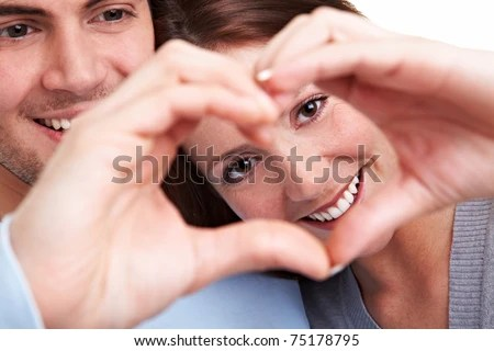 Happy couple in love showing heart with their fingers - stock photo
