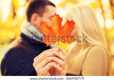 love, relationship, family and people concept - close up of couple with maple leaf kissing in autumn park - stock photo