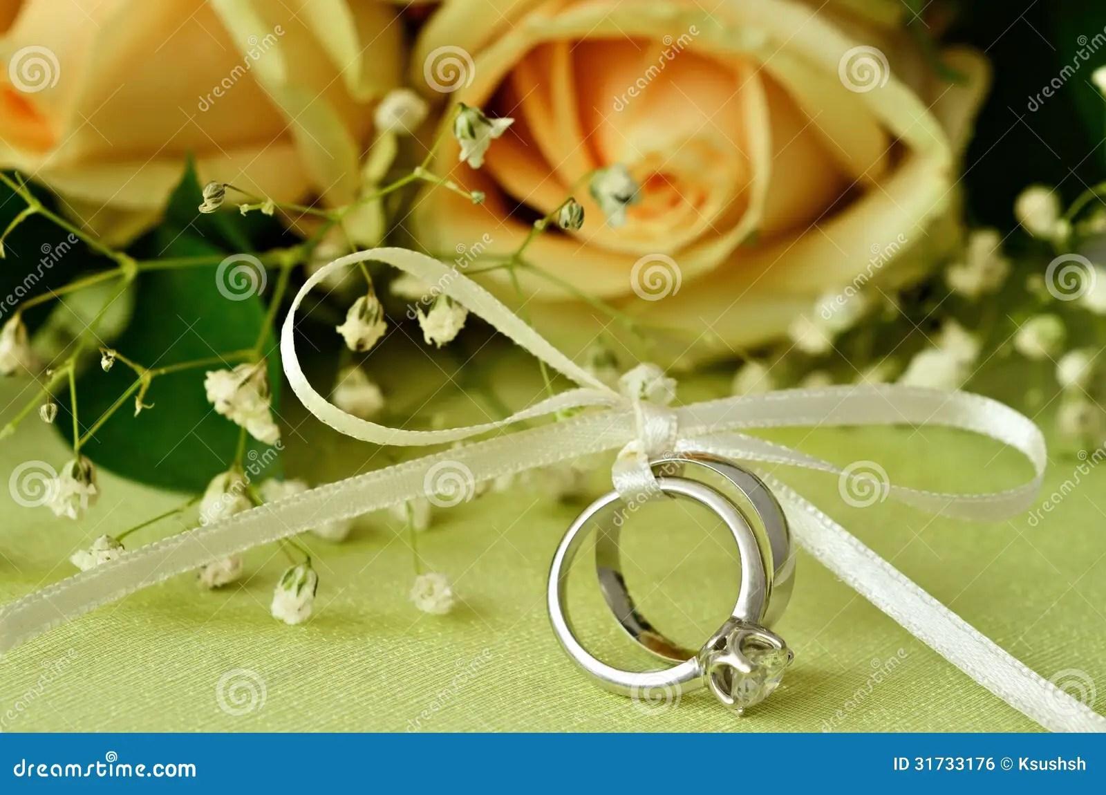 royalty free stock photos gold wedding rings orange roses ribbon image orange wedding rings Bouquet of roses and wedding rings Royalty Free Stock Image