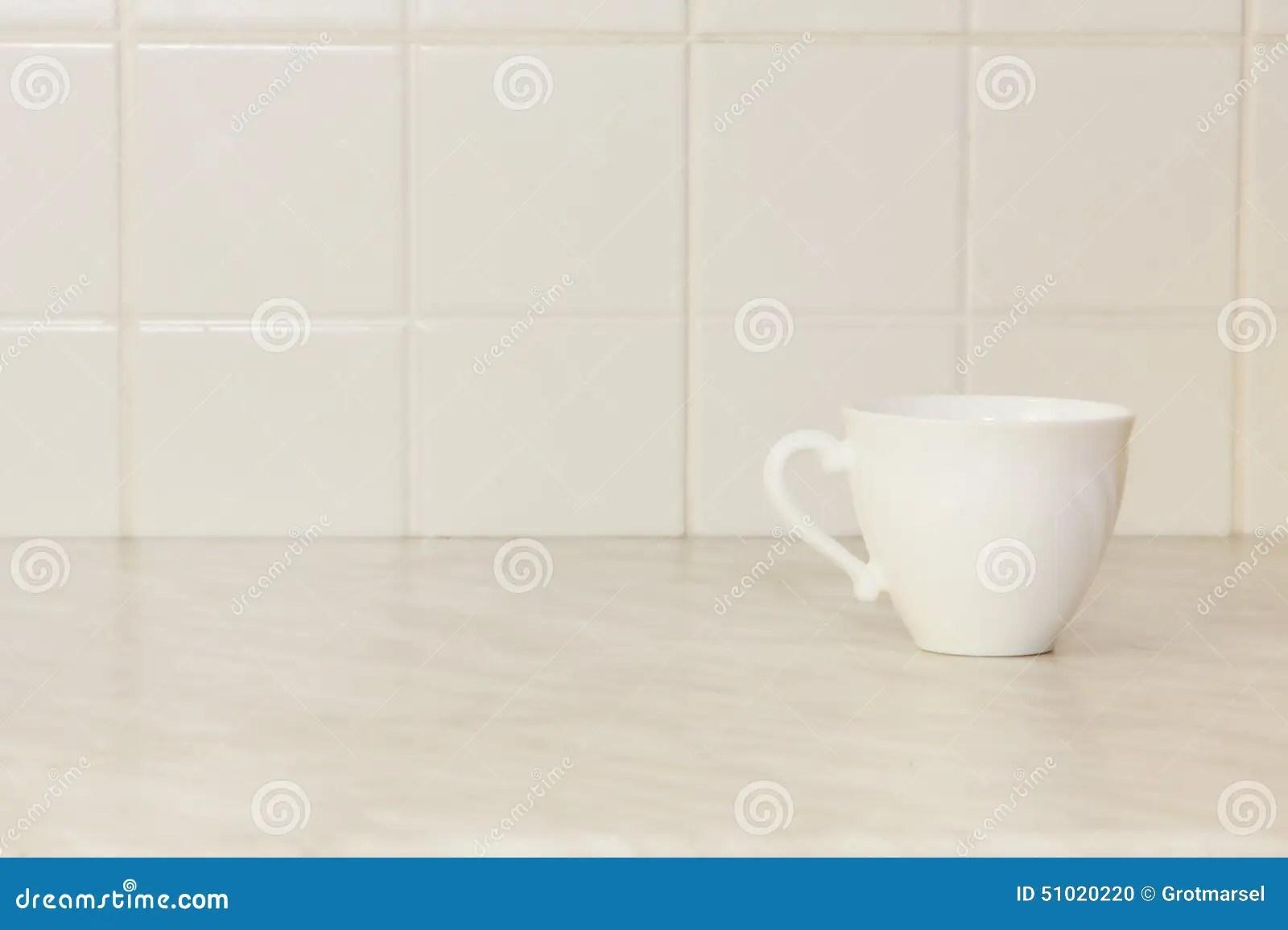 stock photo ceramic tea cup white kitchen table tile background image white kitchen table Ceramic tea cup on white kitchen table