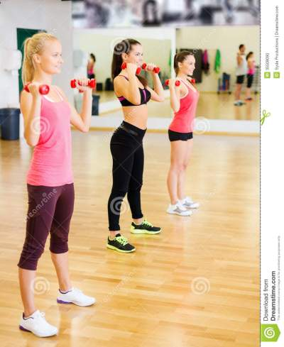 Group Of Smiling People Working Out With Dumbbells Stock ...