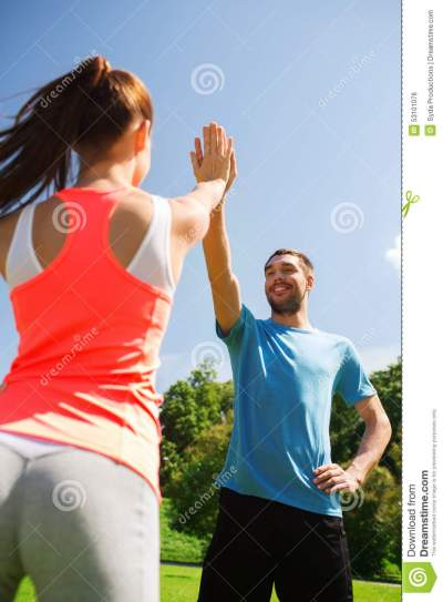 Two Smiling People Making High Five Outdoors Stock Photo ...