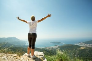 Woman with raised up hands enjoying sunny day,  mountains landscape