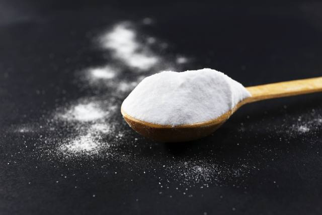 Spoon of baking soda on black background