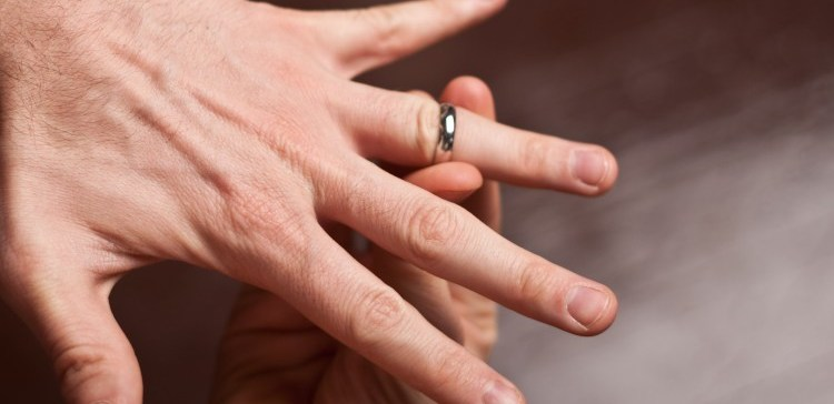 Ring being placed onto man's finger stuck