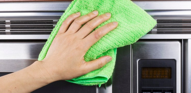 Hand with microfiber cleaning vents of microwave oven